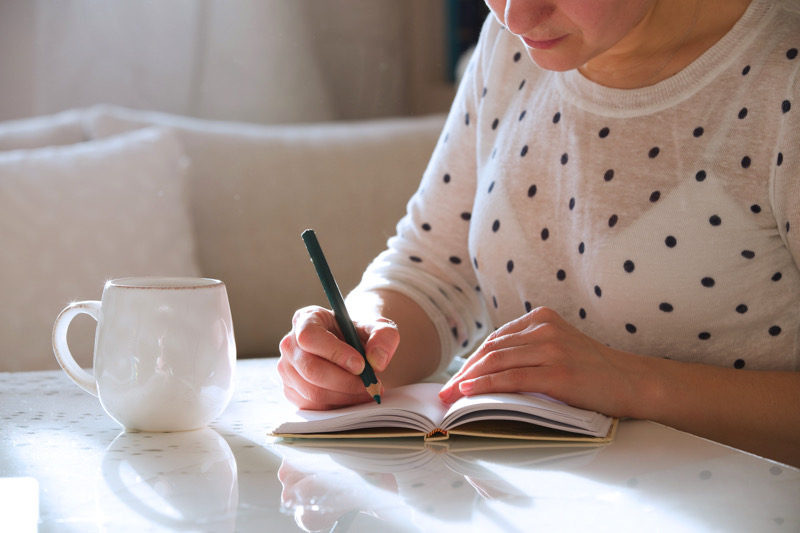 Write down affirmations that touch you in a journal.  | shutterstock.com